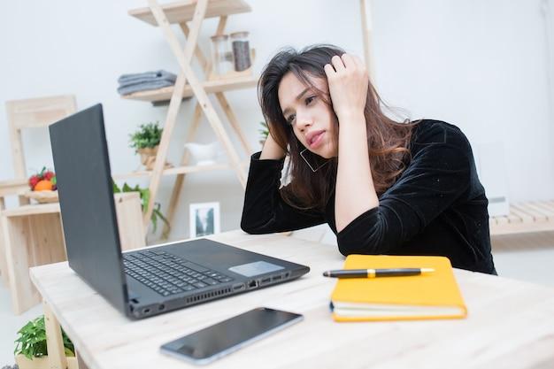 Bella studentessa asiatica sorridente che impara dal servizio di istruzione online, giovane donna asiatica che guarda un computer portatile confusa sul suo lavoro d'affari