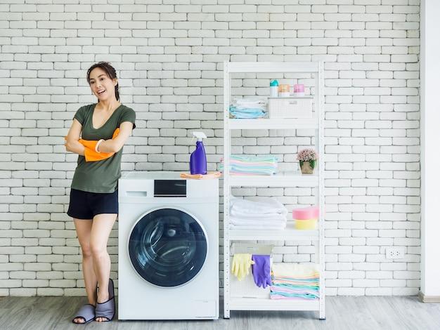 Bella donna asiatica sorridente, casalinga felice che indossa guanti di gomma protettivi arancioni in piedi con le braccia piegate accanto alla lavatrice sul muro di mattoni bianchi