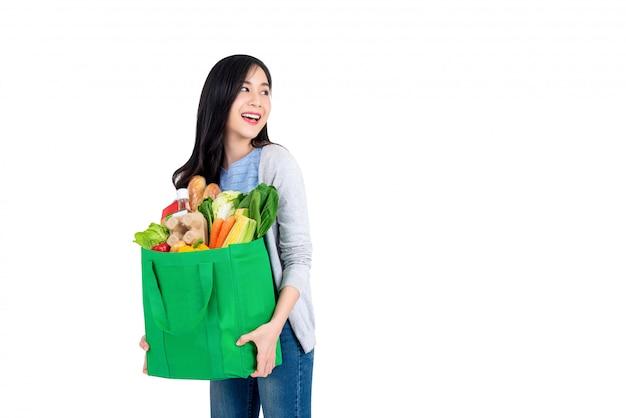 Bella donna asiatica sorridente che giudica il sacchetto della spesa verde riutilizzabile pieno di drogherie e che guarda per copiare lo spazio da parte isolato su fondo bianco