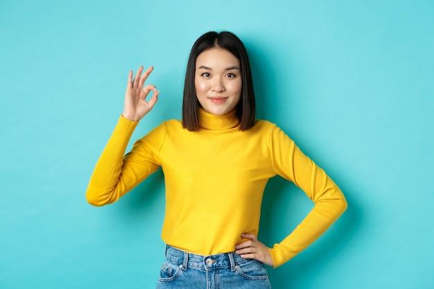 La bella donna asiatica sorridente consiglia il prodotto, mostra il segno ok e sembra soddisfatta, in piedi su sfondo blu