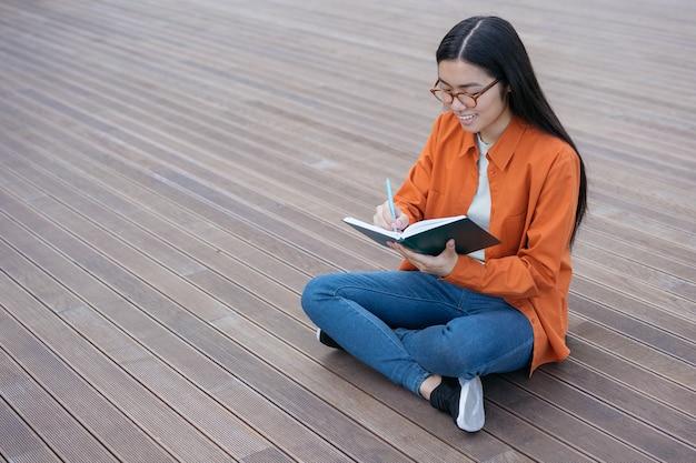 Bella donna asiatica sorridente che scrive nota studente felice che studia concetto di istruzione