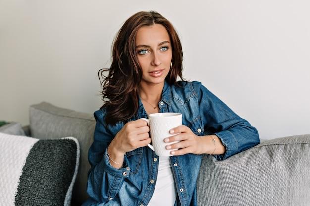 Bella donna attraente sorridente con la pelle abbronzata e un grande sorriso rilassante su un divano nella sua moderna casa accogliente