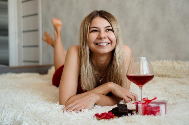 Una bella bionda sorridente giace a letto. san valentino mattina. un bicchiere di vino, cioccolato, dolci e un regalo accanto alla ragazza. buongiorno innamorato