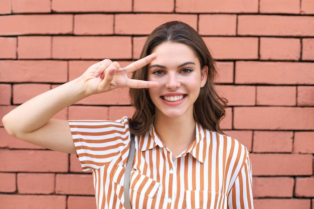 Bella modella bruna sorridente vestita in abiti estivi hipster. donna divertente e positiva che si diverte.