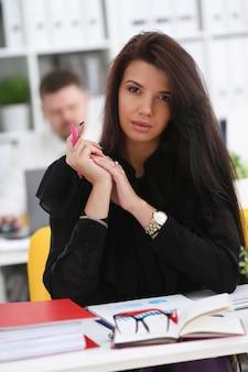 Bella donna sorridente del brunette che si siede al tavolo di lavoro