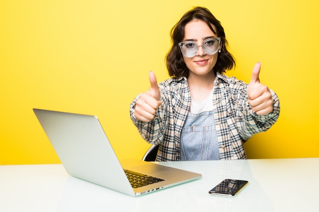 Bella donna d'affari sorridente o studente seduto al suo laptop con un libro aperto insieme a un gesto di pollice in alto