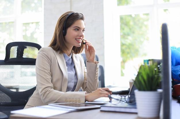 Il bellissimo lavoratore di call center sorridente in cuffia sta lavorando in un ufficio moderno.