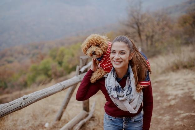 Bella bruna sorridente caucasica vestita casual camminando in natura in autunno e portando il suo cane sulle spalle.