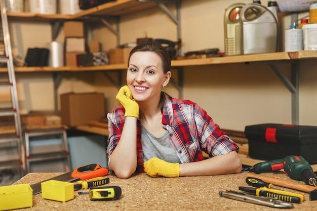Bella sorridente caucasica giovane donna dai capelli castani in camicia a quadri, maglietta grigia, guanti gialli che lavora nel laboratorio di falegnameria al tavolo di legno con strumenti di lavoro da uomo diverso. parità dei sessi.