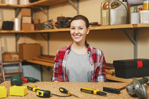 Bella sorridente caucasica giovane donna dai capelli castani in camicia a quadri, maglietta grigia, guanti gialli che lavora nel laboratorio di falegnameria al tavolo di legno con un pezzo di legno, strumenti di lavoro da uomo diverso.