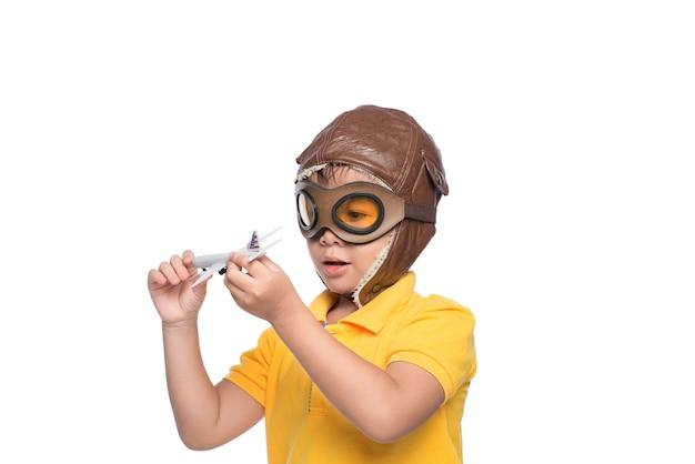 Bello ragazzo sorridente del bambino in casco su un fondo bianco che gioca con un aereo.