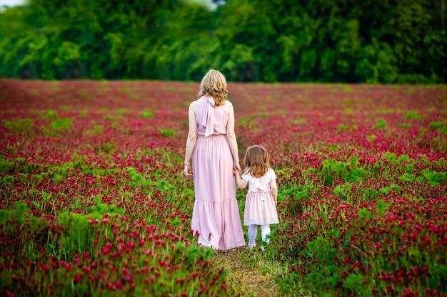 La bella ragazza sorridente del bambino con la giovane madre in famiglia guarda nel campo dei fiori del trifoglio nel tempo del tramonto