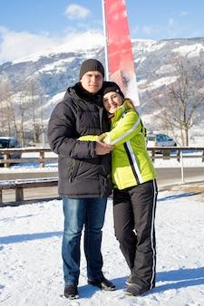 Bella coppia sorridente che abbraccia sulla località di soggiorno invernale alle alpi austriache