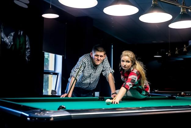 Bella coppia sorridente in pub giocando a biliardo