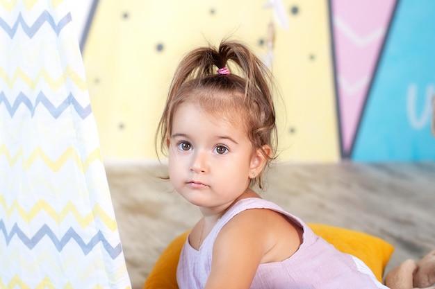 Bellissimo bambino carino sorridente. faccia di bebè. infanzia, concetto di infanzia - bellissimo bambino felice. bambino sorpreso con grandi occhi aperti. una bambina in un vestito rosa gioca con i giocattoli a casa.