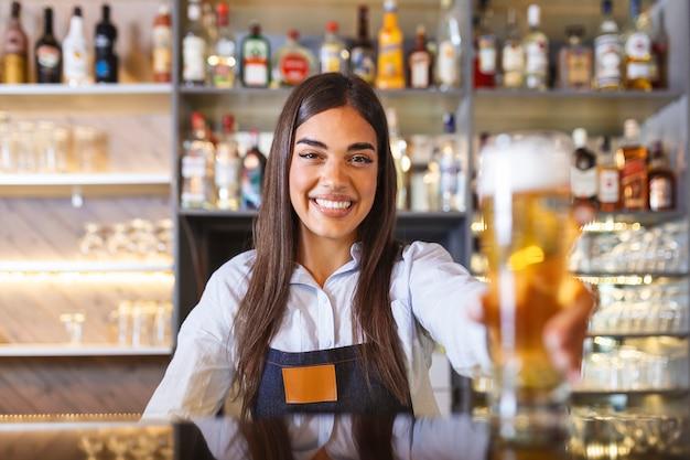 Bella donna sorridente barista che serve una birra alla spina al bancone del bar, scaffali pieni di bottiglie con alcol sullo sfondo