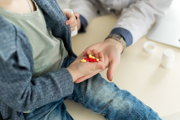 Il bello medico femminile sorridente tiene nella bottiglia della pillola delle armi e la offre al primo piano del visitatore del bambino.
