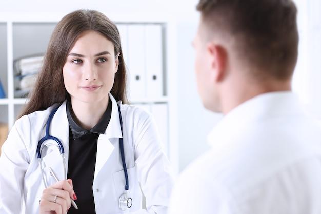Il bello medico femminile sorridente tiene la penna d'argento che riempie l'elenco di storia paziente negli appunti