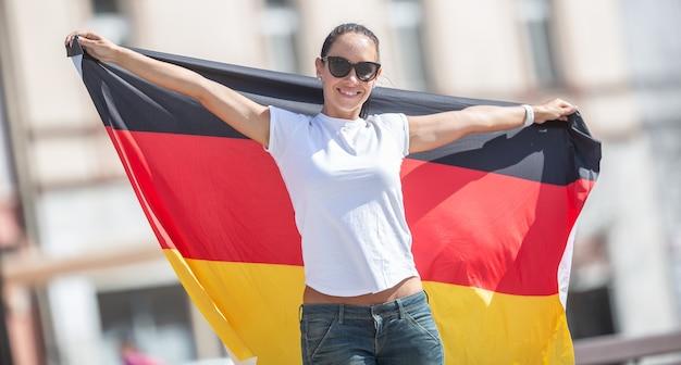 La bella fan femminile sorridente in occhiali da sole tiene una bandiera tedesca dietro di lei all'aperto.