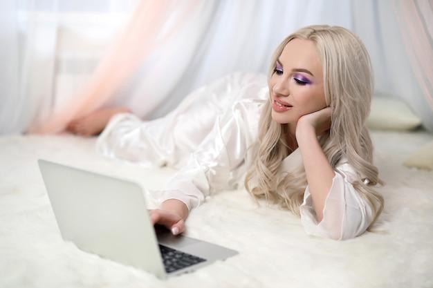 Bella ragazza sorridente in camera da letto utilizzando il suo laptop online.