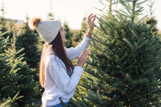 La bella ragazza sorridente sceglie un albero di natale in una piantagione prima delle vacanze invernali.