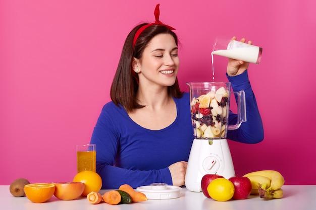 La bella ragazza sorridente cucina i frullati nella mattina.