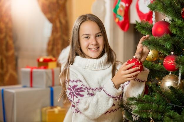 Bella ragazza sorridente che decora l'albero di natale con le palline