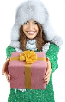Bella ragazza sorridente in cappello con regalo isolato su bianco