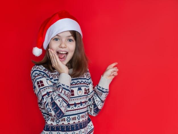 Bella ragazza sorridente in un maglione di capodanno e cappello da babbo natale pubblicità capodanno e concetto di natale