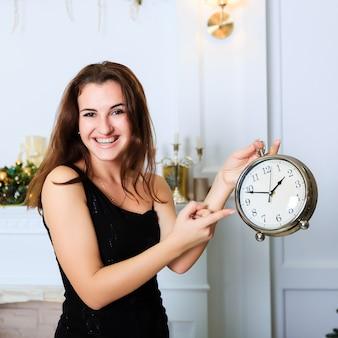 La bella ragazza sorridente mostra l'orologio nell'interno di natale