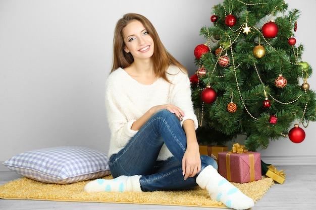 Bella ragazza sorridente seduta vicino all'albero di natale in camera
