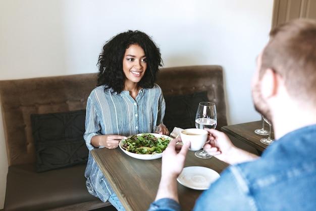 Bella ragazza sorridente che si siede al ristorante con un amico e mangia insalata. signora abbastanza afroamericana che mangia insalata a pranzo