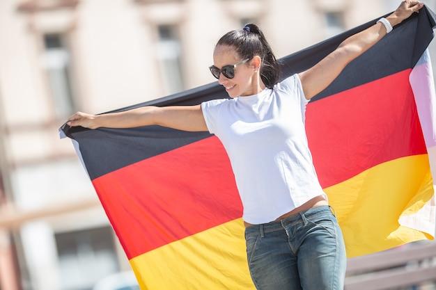 La bella ragazza sorridente in occhiali da sole tiene una bandiera tedesca dietro di lei all'aperto.