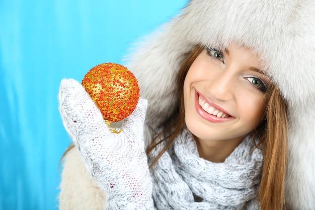 Bella ragazza sorridente con palla di natale