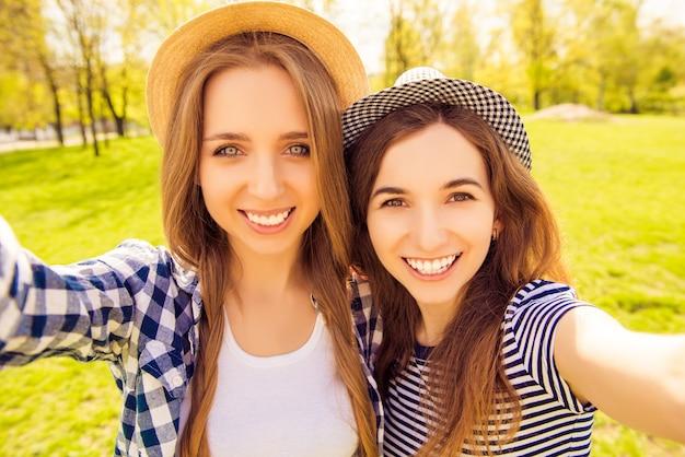 Belle ragazze sorridenti in cappelli che prendono selfie nel parco