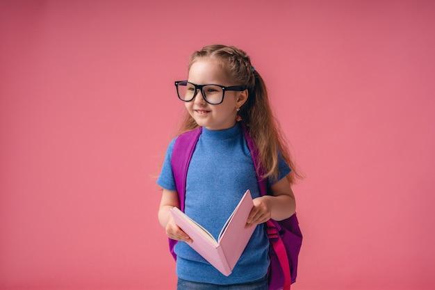Bella bambina sorridente con gli occhiali e in possesso di un libro con una borsa di scuola