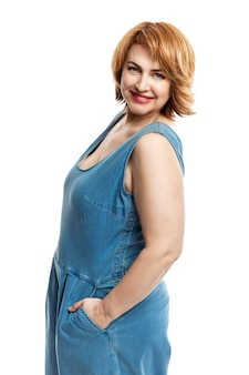 Bella sorridente donna di mezza età con i capelli rossi in tuta di jeans