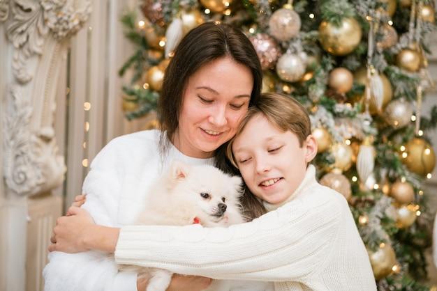 Bella mamma sorridente e figlio che si abbracciano con un cane bianco felice a casa per le vacanze di natale felice fa...