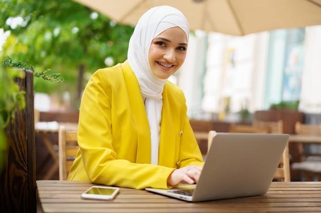 Bella donna musulmana sorridente con il computer portatile al caffè