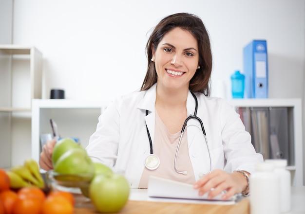 Bella donna sorridente nutrizionista con frutti sani