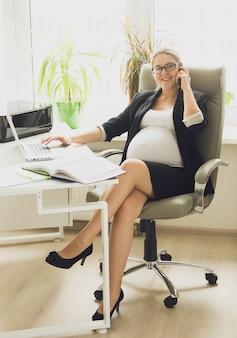 Bella donna incinta sorridente in abito nero che parla al telefono in ufficio