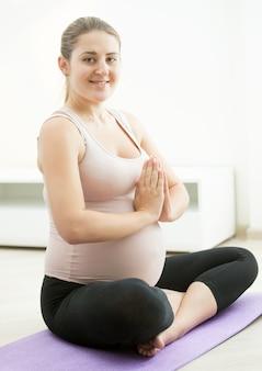 Bella donna incinta sorridente che si siede nella posizione del loto di yoga