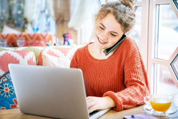 Bella ragazza lentigginosa dai capelli rossi sorridente che lavora con il computer portatile al ristorante tavolo durante una conversazione al telefono. la luce del sole dalla finestra vicina, i capelli ricci in una crocchia.