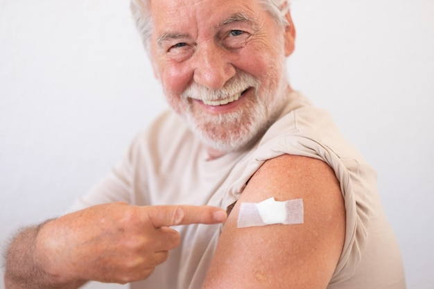Bellissimo uomo anziano sorridente degli anni '70 dopo aver ricevuto il vaccino contro il coronavirus covid-19.