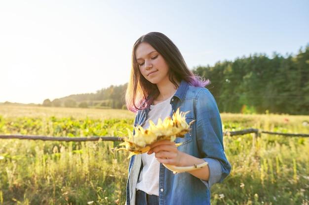 Bella ragazza sorridente dell'adolescente con il girasole della pianta con i semi maturi. paesaggio di campagna scenico, ora d'oro, spazio di copia