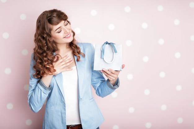 Bella donna sorridente in giacca blu tiene confezione regalo con i capelli ricci