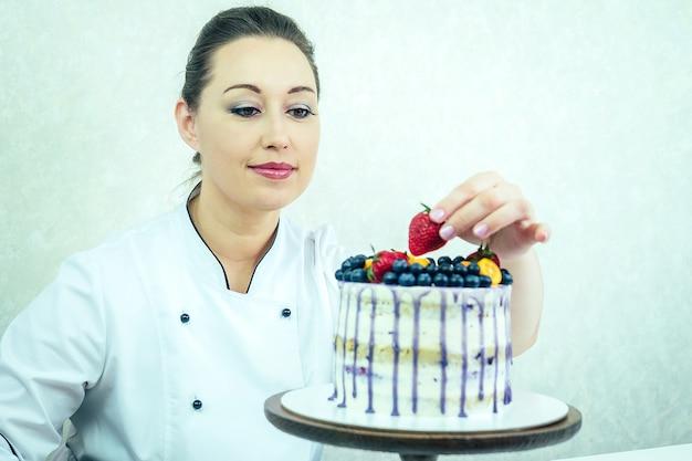Bella e sorridente pasticciera in uniforme da lavoro bianca adorna la torta in cucina. pasticcere, torta, cucina. torta nuziale e di compleanno con frutti di bosco.