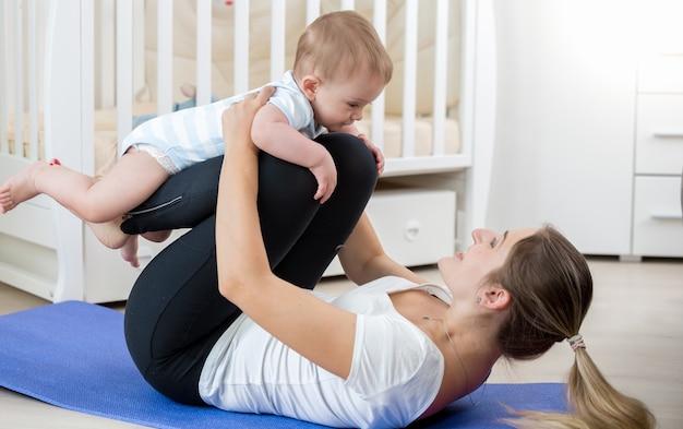 Bella donna sorridente che fa esercizio di yoga con il suo bambino in soggiorno
