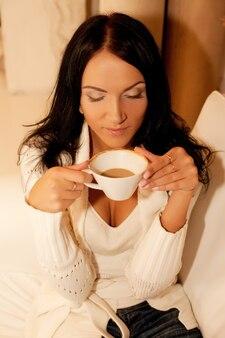 Bella donna sorridente che beve caffè. casa.