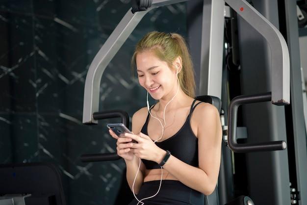 Una bella donna sorridente in auricolari utilizzando un social network e ascoltando musica in palestra, fitness e concetto di tecnologia